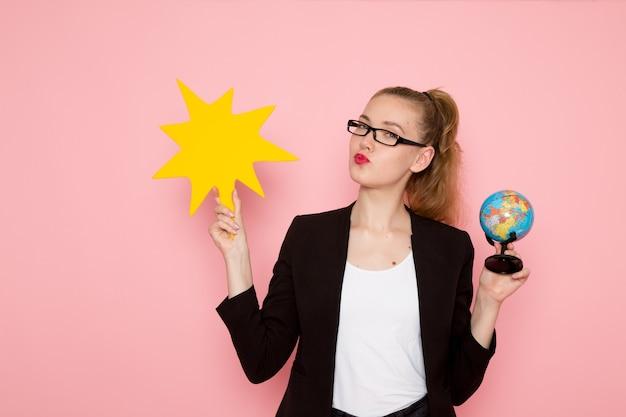 Vue de face de l'employée de bureau en veste noire stricte tenant un grand panneau jaune avec globe sur mur rose