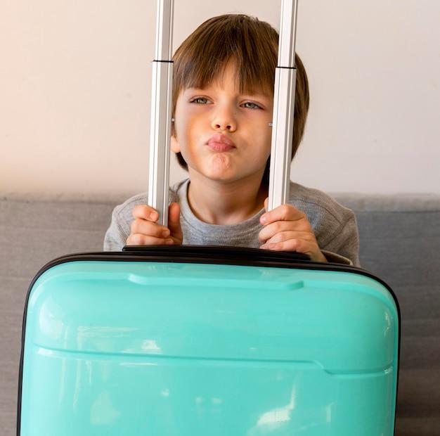 Vue de face de l'enfant avec des bagages