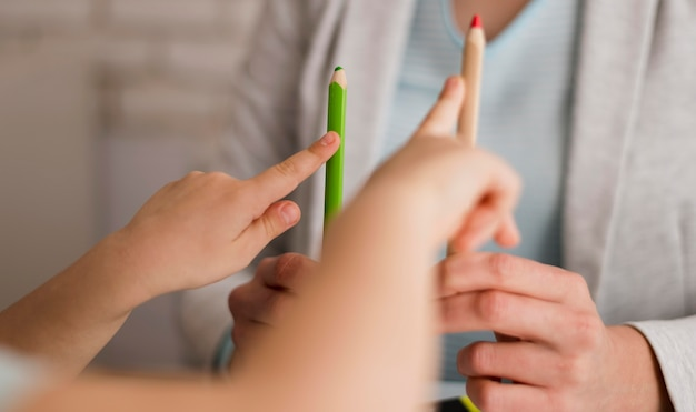Vue de face d'un enfant comptant à la maison à l'aide de crayons