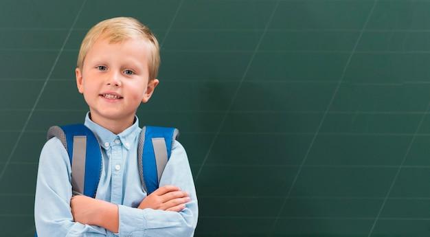 Vue de face enfant debout à côté d'un tableau noir