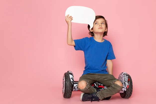 Une vue de face enfant garçon adorable doux en t-shirt bleu assis sur le segway sur le plancher rose