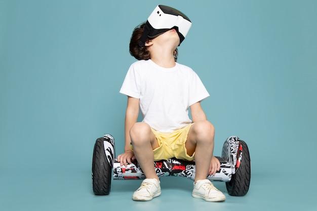 Une vue de face enfant garçon mignon adorable doux jouant vr sur segway sur le plancher bleu