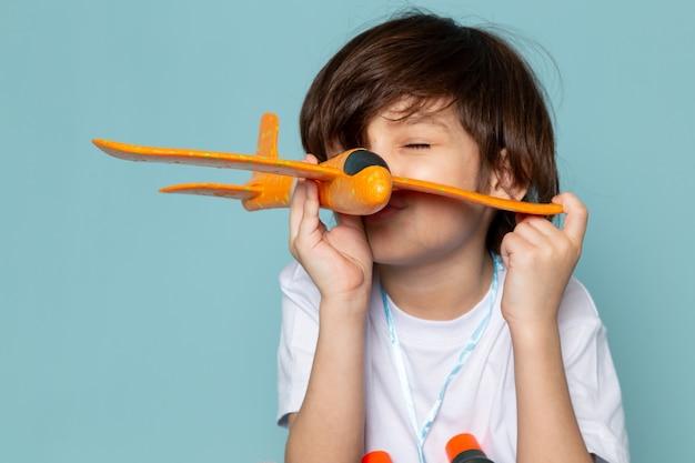 Vue de face enfant garçon mignon adorable jouant avec jouet avion orange sur le bureau bleu