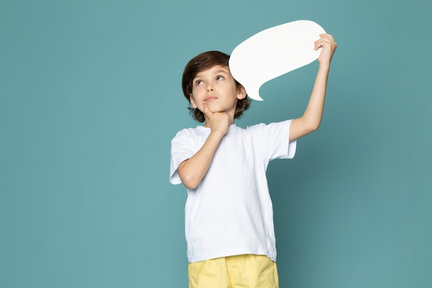 Une vue de face enfant garçon mignon adorable en t-shirt blanc sur le sol bleu