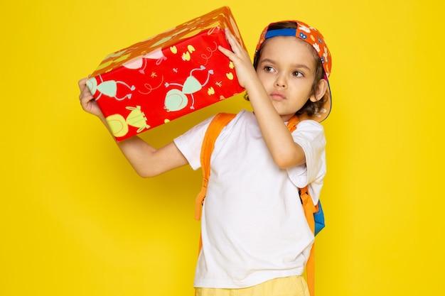 Vue de face enfant garçon en t-shirt blanc et casquette de baseball tenant rouge conçu présent sur le bureau jaune