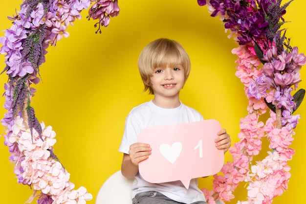 Une vue de face enfant souriant aux cheveux blonds adorable doux mignon sur l'espace jaune