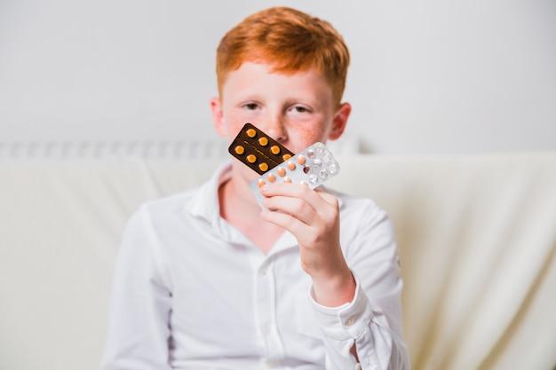 Vue de face enfant tenant des comprimés pilules