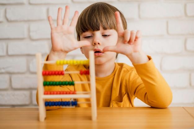 Vue de face d'un enfant utilisant un boulier pour apprendre à compter