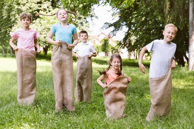 Vue de face des enfants en compétition avec des sacs de jute