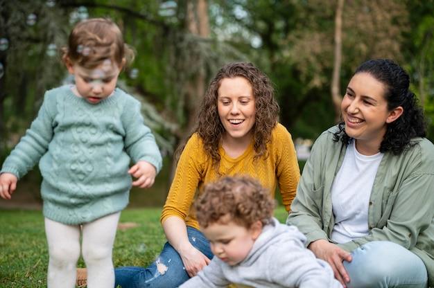 Vue de face des enfants à l'extérieur dans le parc avec les mères lgbt