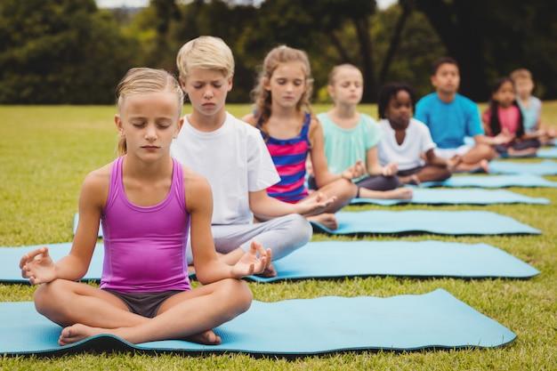 Vue de face des enfants faisant du yoga
