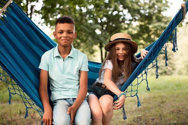 Vue de face d'enfants heureux dans un hamac