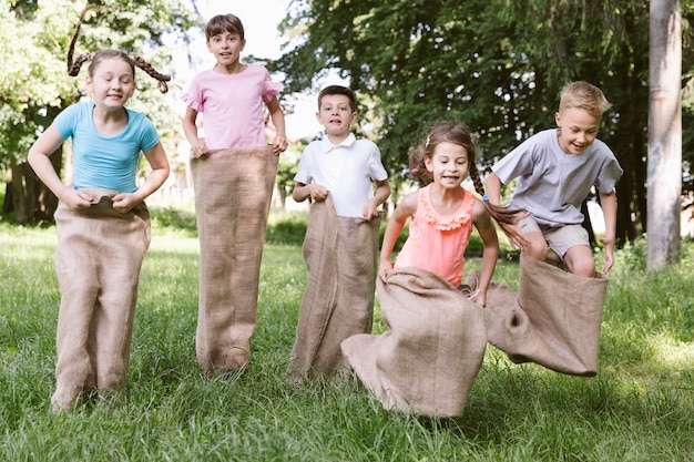 Vue de face des enfants jouant avec des sacs de pommes de terre