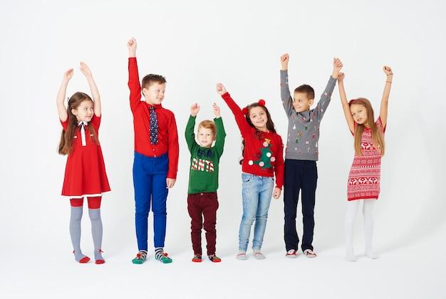 Vue de face des enfants les mains debout dans une rangée