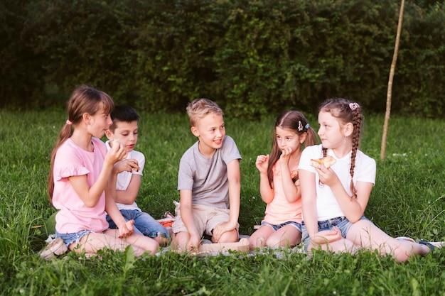 Vue de face des enfants en train de déjeuner