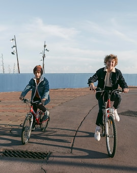 Vue de face des enfants sur les vélos à l'extérieur avec copie espace