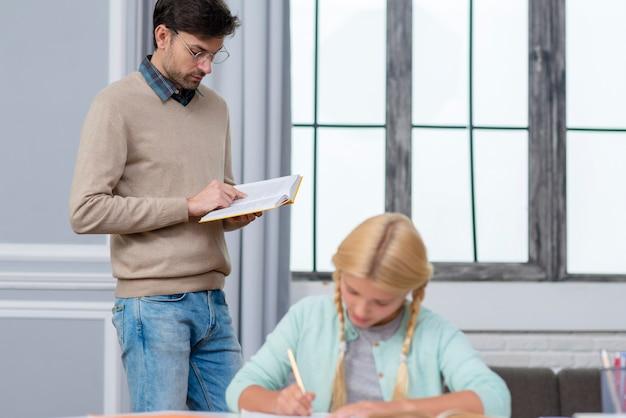 Vue de face enseignant debout et enfant l'écoutant