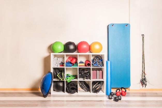 Vue de face de l'équipement de gymnastique disposé sur des étagères au mur. concept d'équipement de gym.