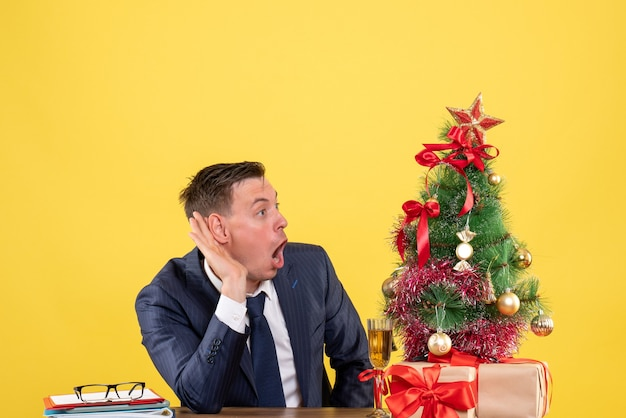 Vue de face étonné homme écoutant quelque chose assis à la table près de l'arbre de noël et présente sur fond jaune