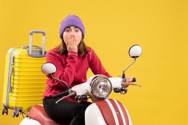 Vue de face étonné jeune femme sur cyclomoteur à l'avant