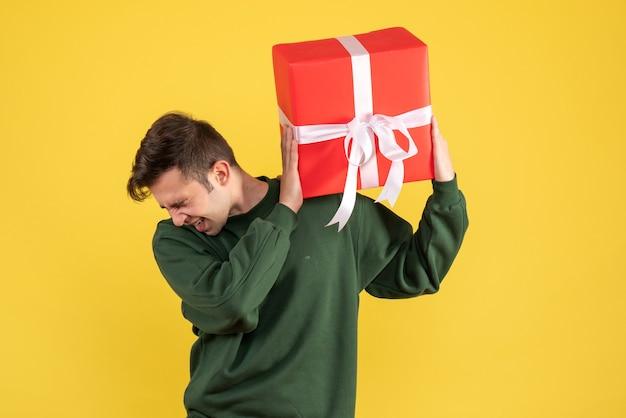 Vue de face étonné jeune homme avec chandail vert tenant cadeau sur jaune