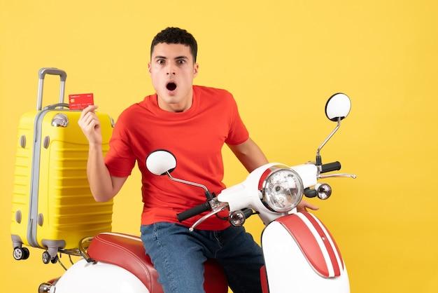 Vue de face étonné jeune homme sur cyclomoteur tenant une carte de crédit