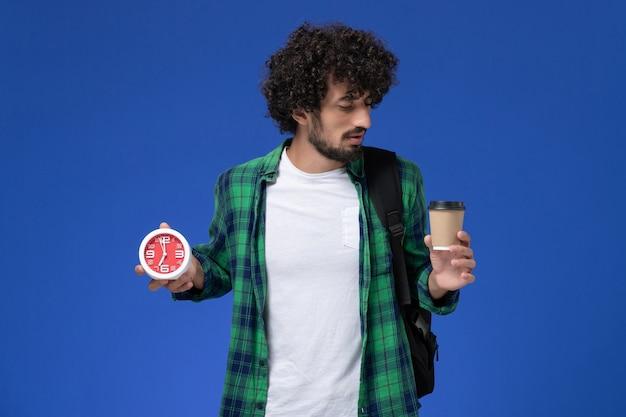 Vue de face de l'étudiant en chemise à carreaux vert portant un sac à dos noir et tenant des horloges et du café sur le mur bleu