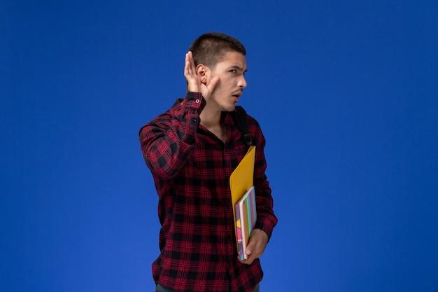 Vue de face de l'étudiant masculin en chemise à carreaux rouge avec sac à dos contenant des fichiers et des cahiers essayant d'entendre sur le mur bleu