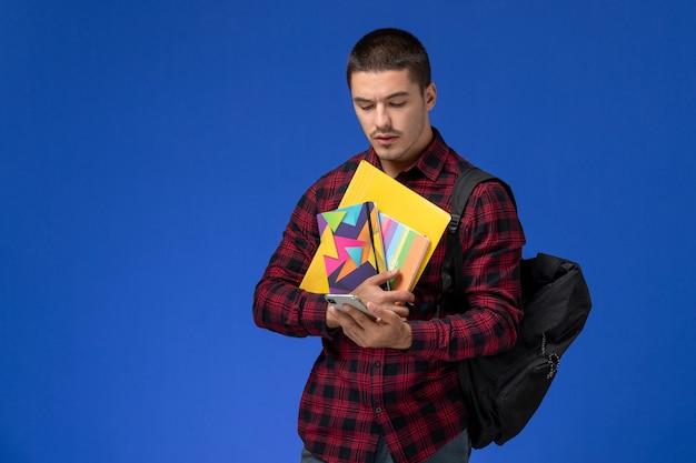 Vue de face de l'étudiant masculin en chemise à carreaux rouge avec sac à dos tenant un cahier et des fichiers à l'aide de son téléphone sur le mur bleu