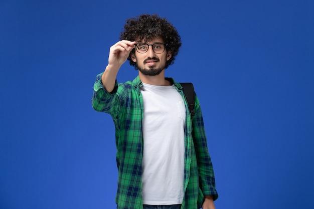 Vue de face de l'étudiant masculin en chemise à carreaux vert souriant sur mur bleu
