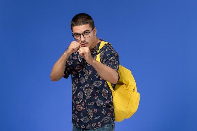 Vue de face de l'étudiant masculin en chemise de coton foncé portant un boxer sac à dos jaune pose sur le mur bleu