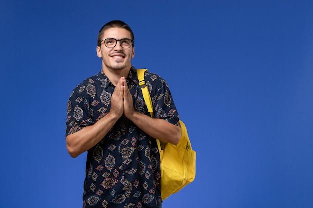 Vue de face de l'étudiant masculin en chemise sombre portant un sac à dos jaune sur le mur bleu