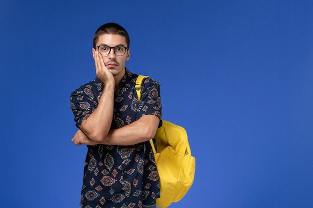 Vue de face de l'étudiant masculin en chemise sombre portant un sac à dos jaune