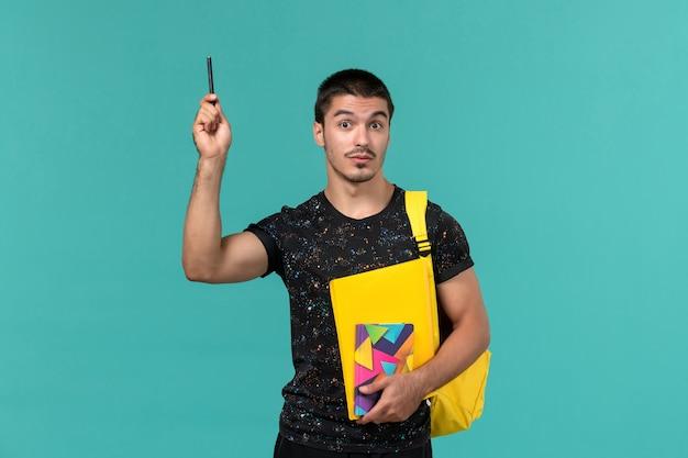 Vue de face de l'étudiant masculin en t-shirt foncé sac à dos jaune tenant un stylo et des fichiers sur le mur bleu clair