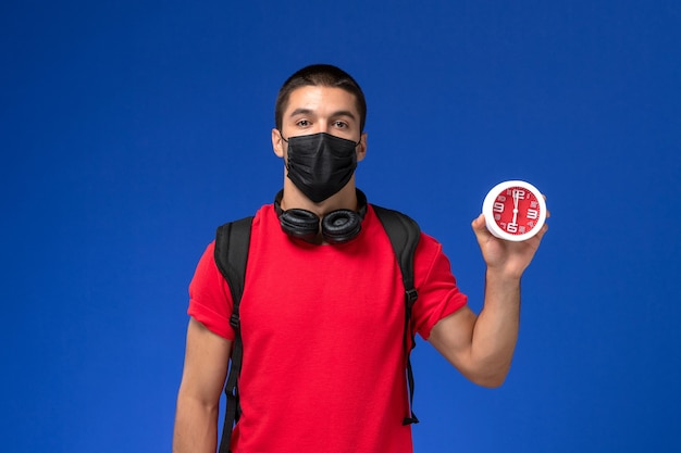 Vue de face étudiant masculin en t-shirt rouge portant un masque avec sac à dos tenant des horloges sur le fond bleu.