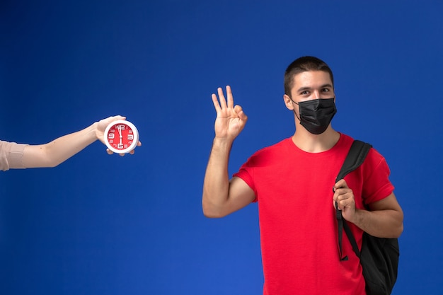 Vue de face étudiant masculin en t-shirt rouge portant un sac à dos avec masque posant sur le fond bleu.