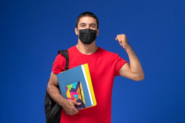 Vue de face étudiant masculin en t-shirt rouge portant un sac à dos en masque stérile noir tenant un cahier et des fichiers sur le fond bleu.