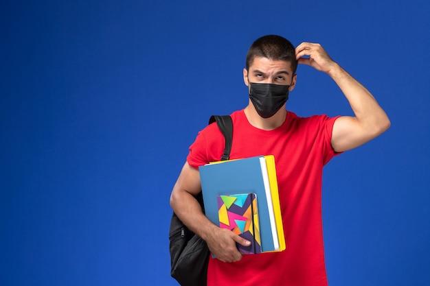 Vue de face étudiant masculin en t-shirt rouge portant sac à dos en masque stérile noir tenant des fichiers et de la pensée sur fond bleu.