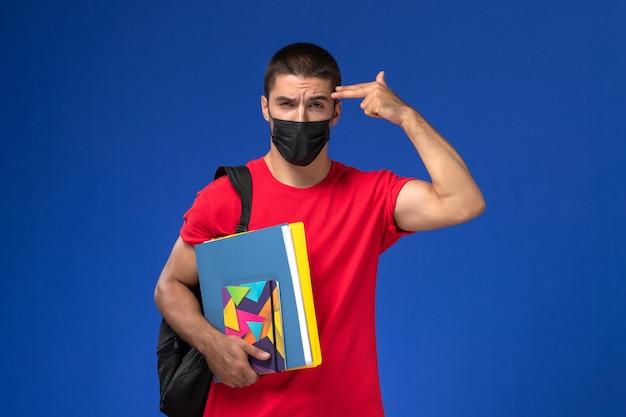 Vue de face étudiant masculin en t-shirt rouge portant sac à dos en masque stérile noir tenant des fichiers posant sur fond bleu.