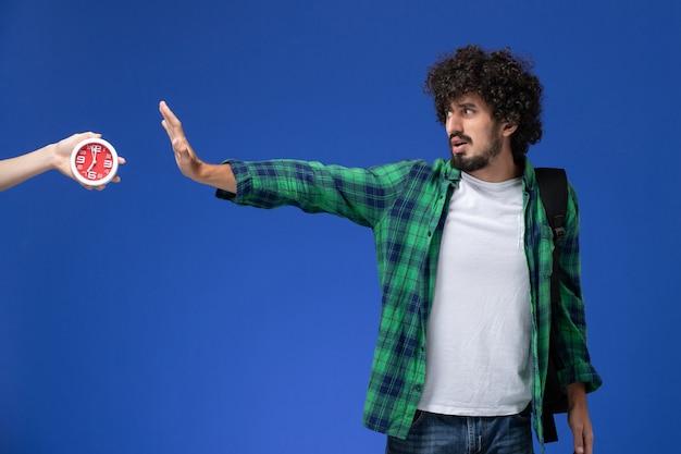 Vue de face d'un étudiant portant un sac à dos noir posant avec une expression confuse sur le mur bleu clair