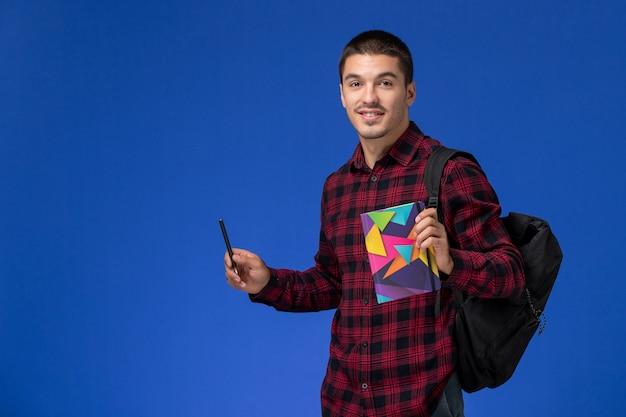 Vue de face de l'étudiant de sexe masculin en chemise à carreaux rouge avec sac à dos tenant un cahier et un stylo sur un mur bleu clair