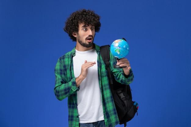Vue de face de l'étudiant de sexe masculin en chemise à carreaux vert portant un sac à dos noir et tenant petit globe sur mur bleu