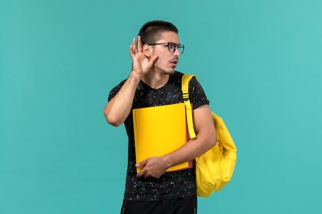 Vue de face de l'étudiant de sexe masculin en t-shirt foncé sac à dos jaune tenant différents fichiers essayant d'entendre sur mur bleu clair