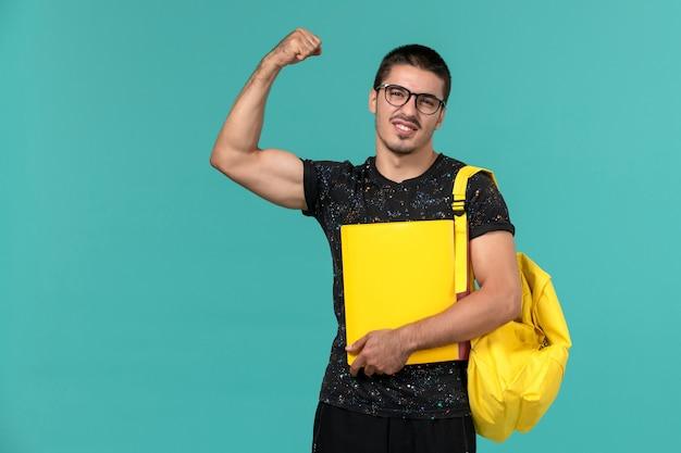 Vue de face de l'étudiant de sexe masculin en t-shirt foncé sac à dos jaune tenant différents fichiers fléchissant sur le mur bleu clair