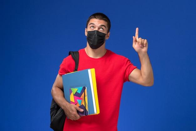 Vue de face étudiant de sexe masculin en t-shirt rouge portant sac à dos en masque stérile noir tenant des fichiers avec le doigt levé sur le fond bleu.