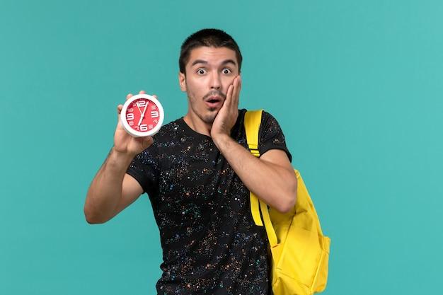 Vue de face de l'étudiant en t-shirt foncé sac à dos jaune tenant des horloges sur le mur bleu clair