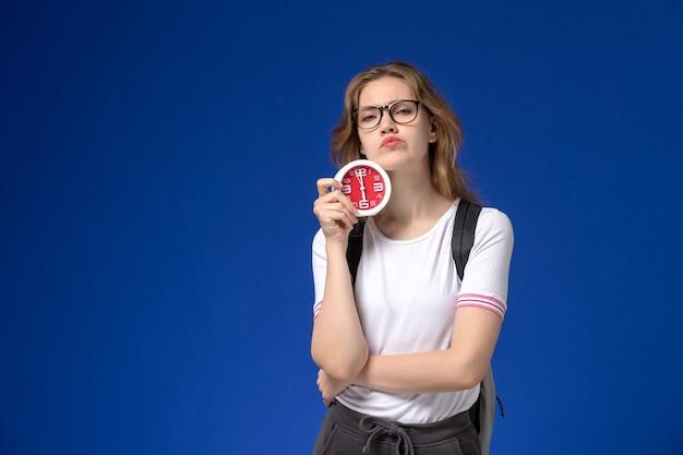 Vue de face de l'étudiante en chemise blanche portant un sac à dos et tenant des horloges avec une expression mécontente sur le mur bleu