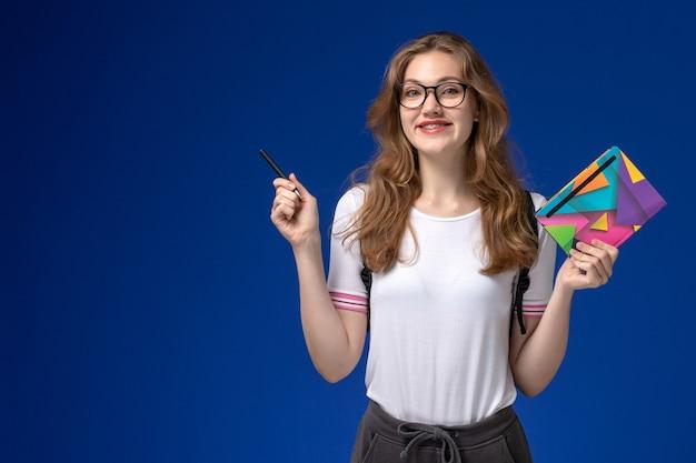 Vue de face de l'étudiante en chemise blanche tenant un stylo et un cahier sur le mur bleu