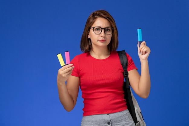Vue de face de l'étudiante en chemise rouge avec sac à dos tenant des feutres sur le mur bleu