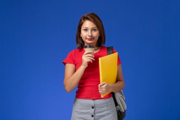 Vue de face de l'étudiante en chemise rouge avec sac à dos tenant des fichiers jaunes et café sur mur bleu